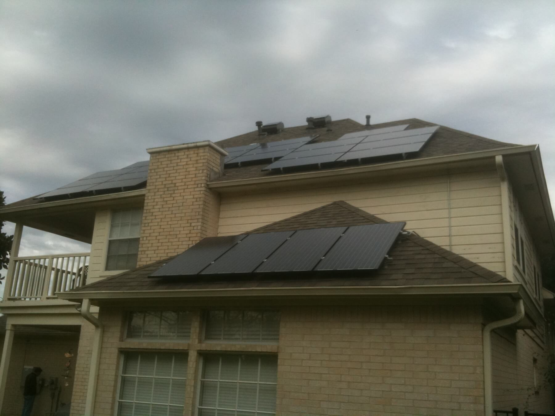 House roof with solar panels under cloudy and gloomy sky