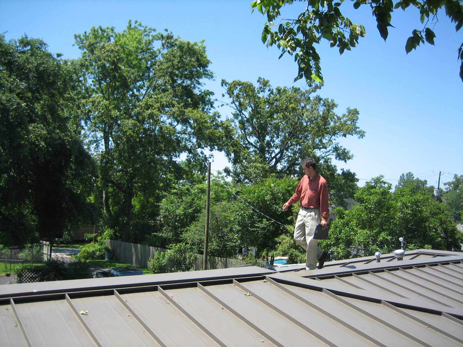 Man checking house roof's condition on a sunny day