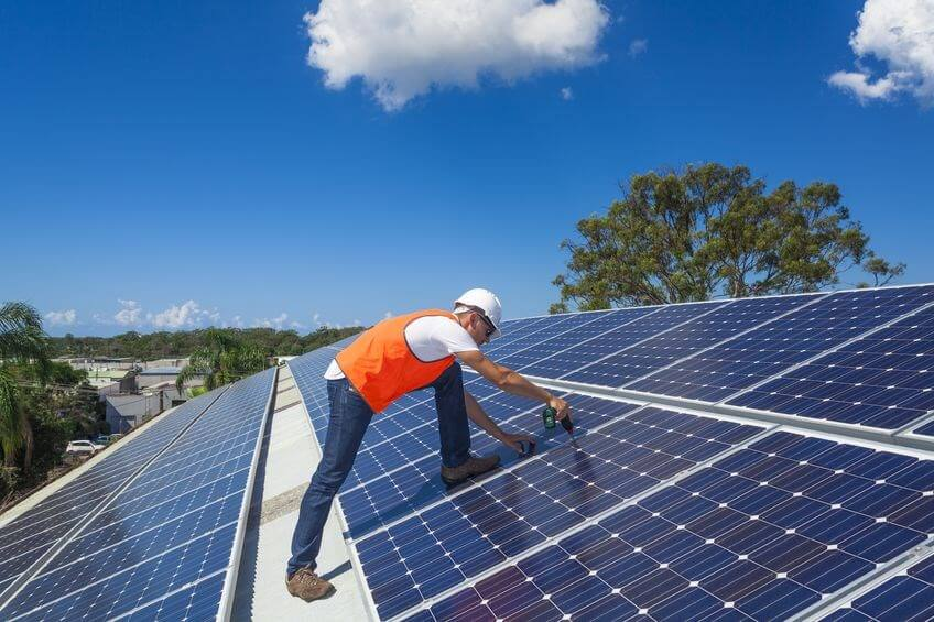 Man working on solar panels on a sunny morning