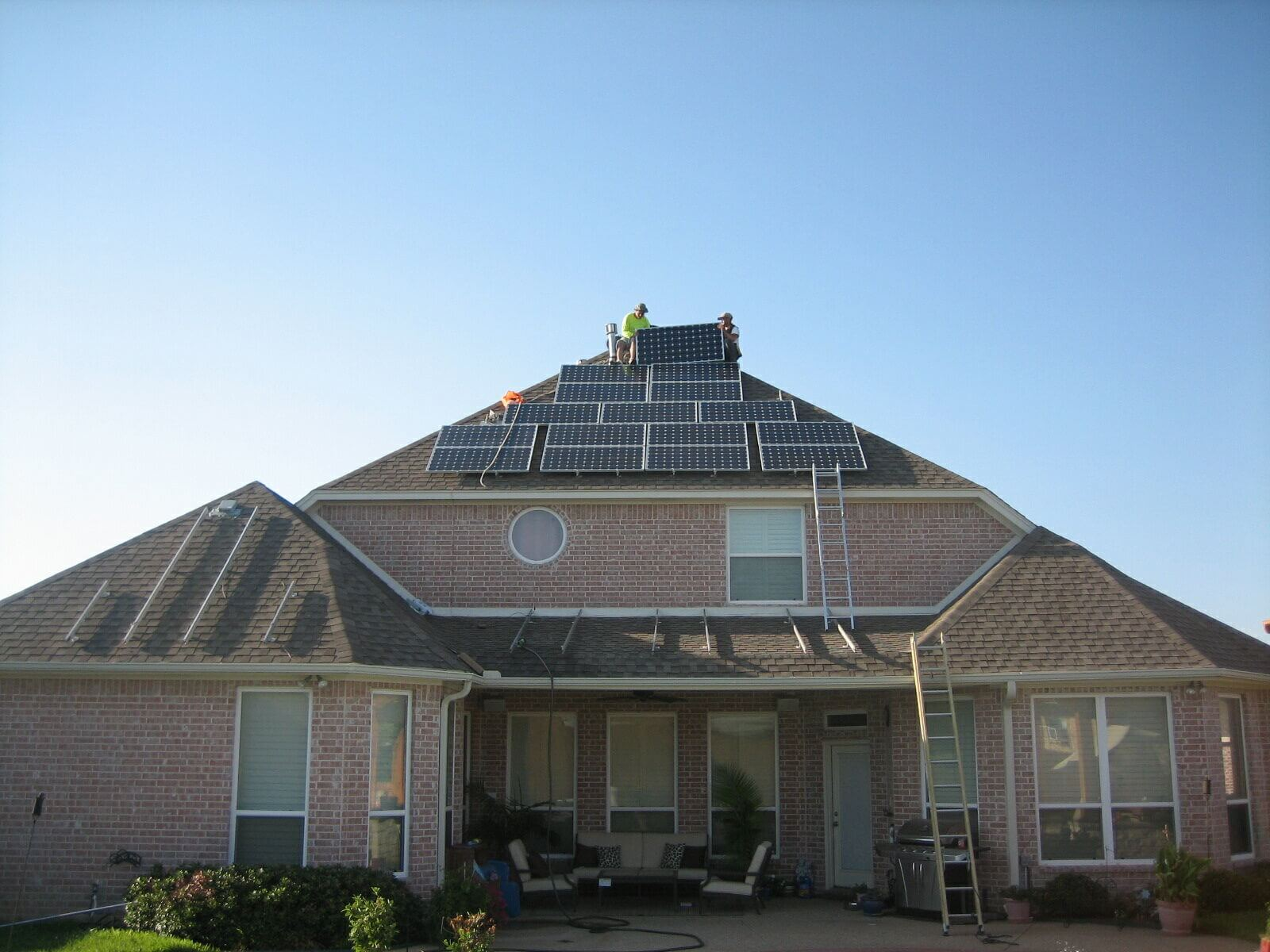 Workers doing maintenance on roof solar panels