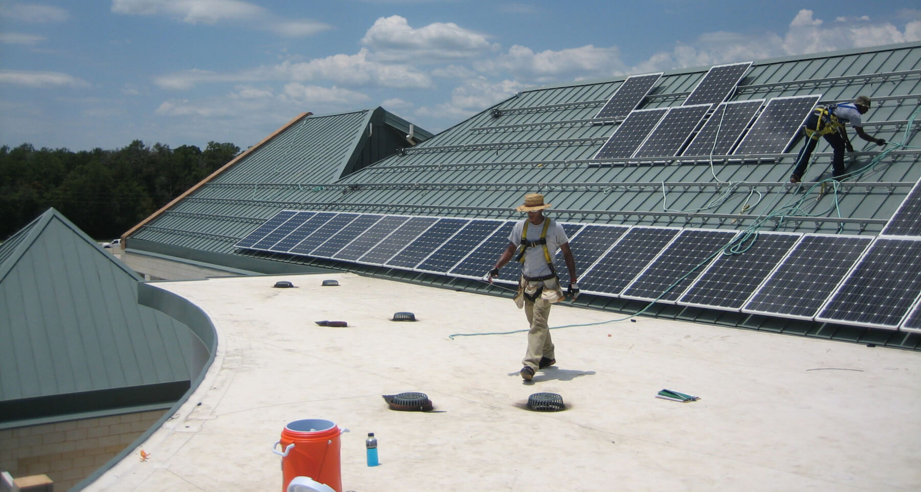 Workers installing solar panels on the roof